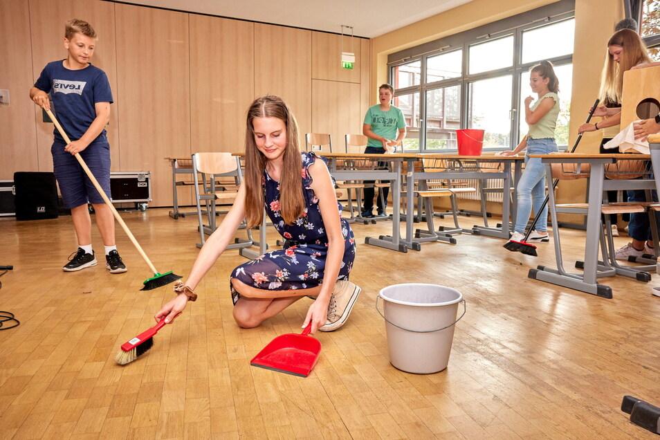 Kehraus mit Lerneffekt: Jonas, Emma, Tim, Tabea und Tarja (v.l.) aus der achten Klasse fegen in einem Klassenzimmer des Pirnaer Herder-Gymnasiums.