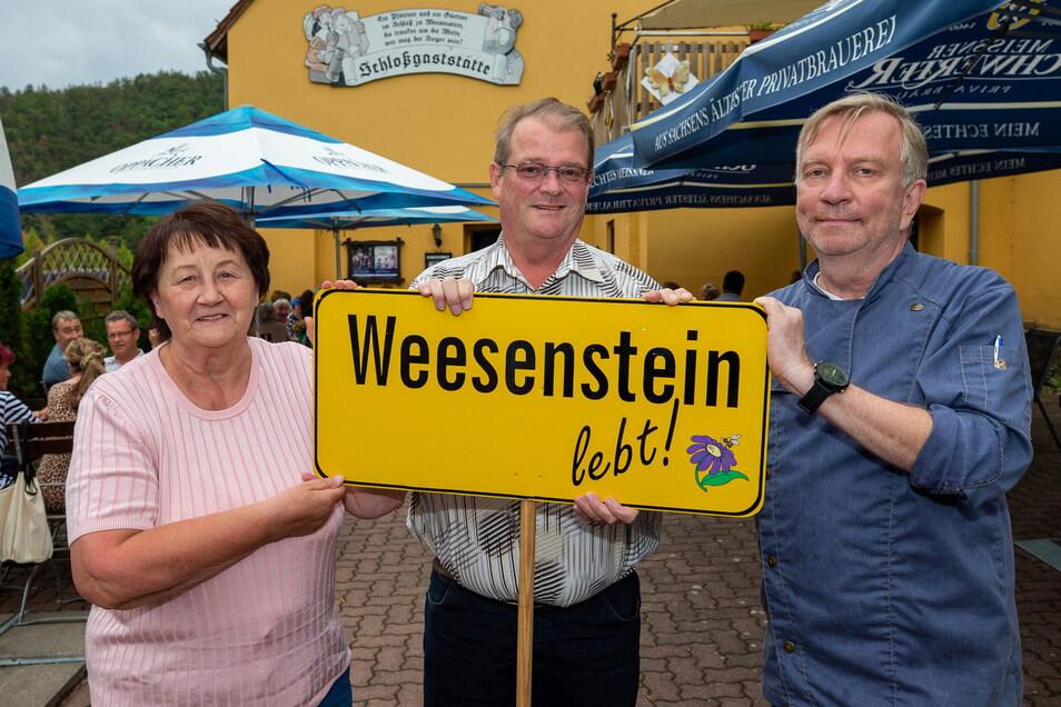 Das Schild, das Weesenstein begleitet - und Roswitha Rehwald, den ehemaligen Bürgermeister Jörg Glöckner sowie Gastwirt Axel Prussak (v.l.).