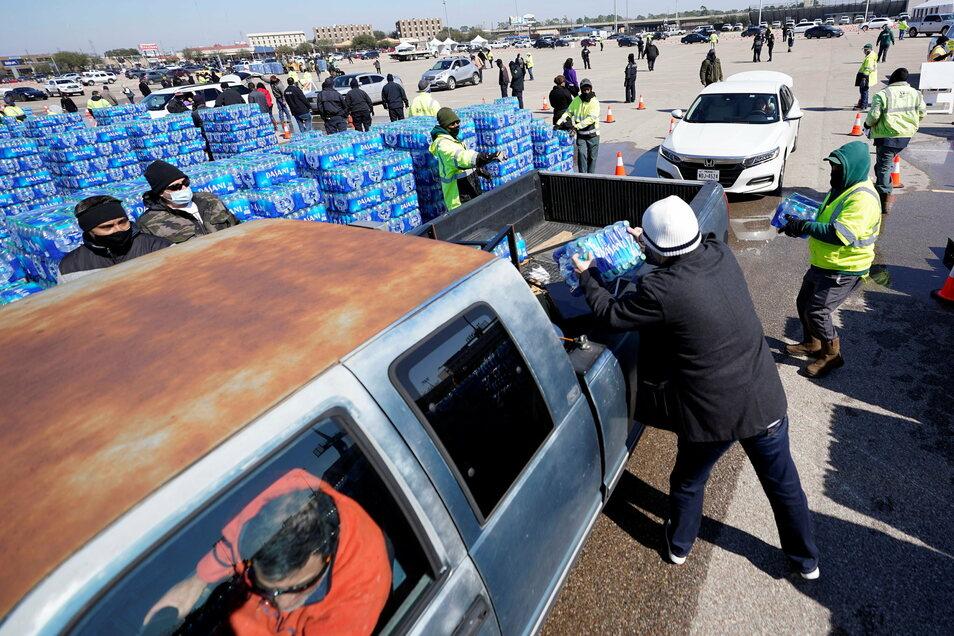 Wasserflaschen werden an einer Verteilungsstelle auf die Ladefläche eines Autos geladen. Helfer verteilen Wasser an Einwohner, nachdem im US-Bundesstaat Texas in Folge einer Kaltfront große Probleme bei der Trinkwasserversorgung herrschten.