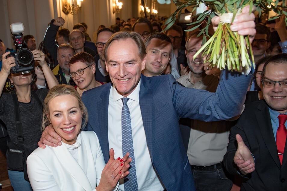Burkhard Jung jubelt mit seiner Frau Ayleena über seinen knappen Sieg. Rechts neben seinem Kopf ist SPD-Landeschef Martin Dulig zu sehen, links davon dessen Ehefrau.