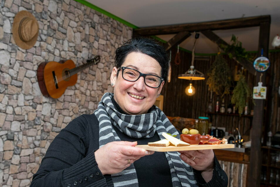 Beatriz Hetzke mit Schinken und Käse inmitten ihres neuen Restaurants in Königstein.