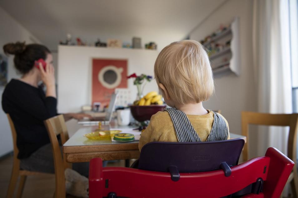 Eine Frau sitzt im Homeoffice an ihrem Laptop und telefoniert, während ihr Kind neben ihr in einem Kinderstuhl am Tisch sitzt.