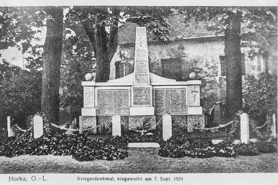 1924 fand die zweite Einweihung statt und wurde auf dieser Postkarte verewigt. Der Obelisk wurde zuvor mit zwei Gedenktafeln und einem Adler ergänzt. Auf den Tafeln stehen die Namen von 64 im Ersten Weltkrieg Gefallenen aus dem Kirchspiel Horka.