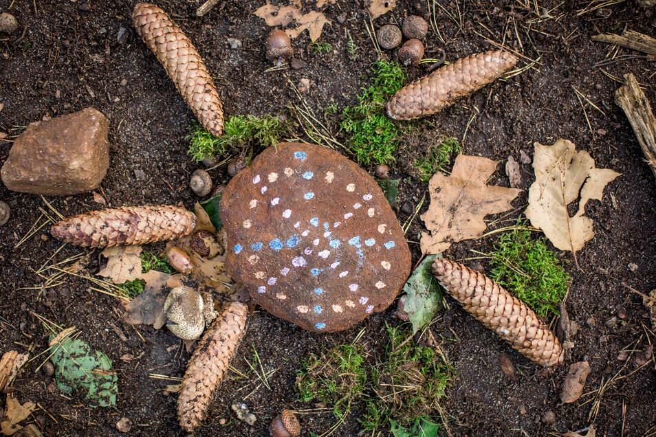 Der Ankommkreis besteht aus einem bemalten Stein und Tannenzapfen.