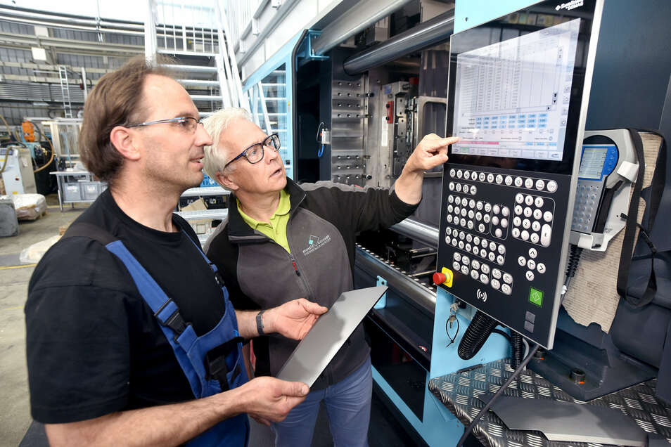 Bernd Nebel, Geschäftsführer von Plastic Concept, und Mitarbeiter Frank Kriegel an einer Spritzgussmaschine.