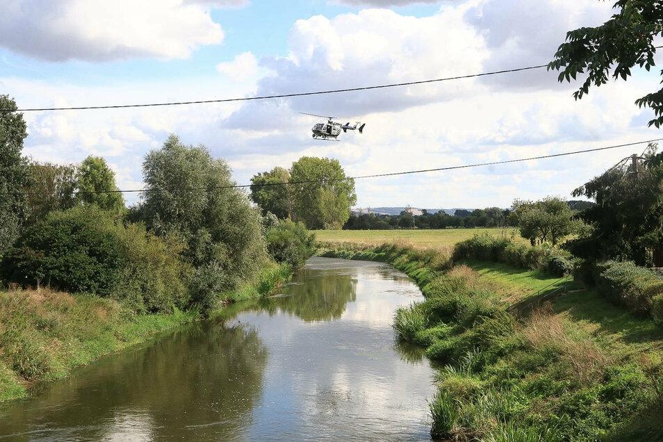 Ein Helikopter überfliegt die Unstrut. Feuerwehrleute suchen seit Sonntagmittag am Flussufer bei Schönewerda (Kyffhäuserkreis) nach einem Krokodil, das eine Pferdebesitzerin gesichtet haben will. Der Landkreis sprach eine öffentliche Warnung aus.