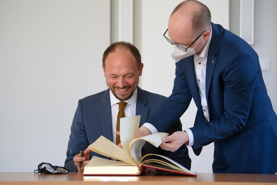 Marco Wanderwitz (CDU, l.), Ostbeauftragter der Bundesregierung, bekommt von David Statnik, Vorsitzender der Domowina, beim Besuch im Haus der Sorben das Goldene Buch der Domowina vorgelegt.