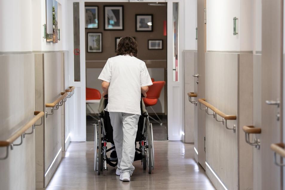Eine Pflegerin schiebt eine Frau in ihrem Rollstuhl durch den Gang eines Altenheimes.