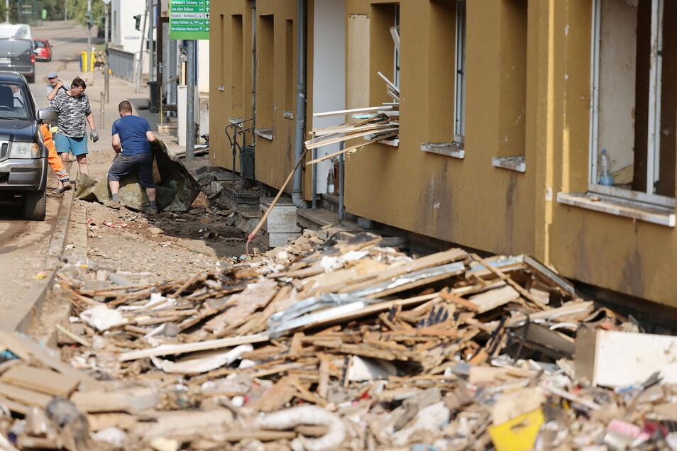 Menschen räumen Schutt aus ihren Häusern. Das Hochwasser hat erhebliche Schäden in der Eifel angerichtet.