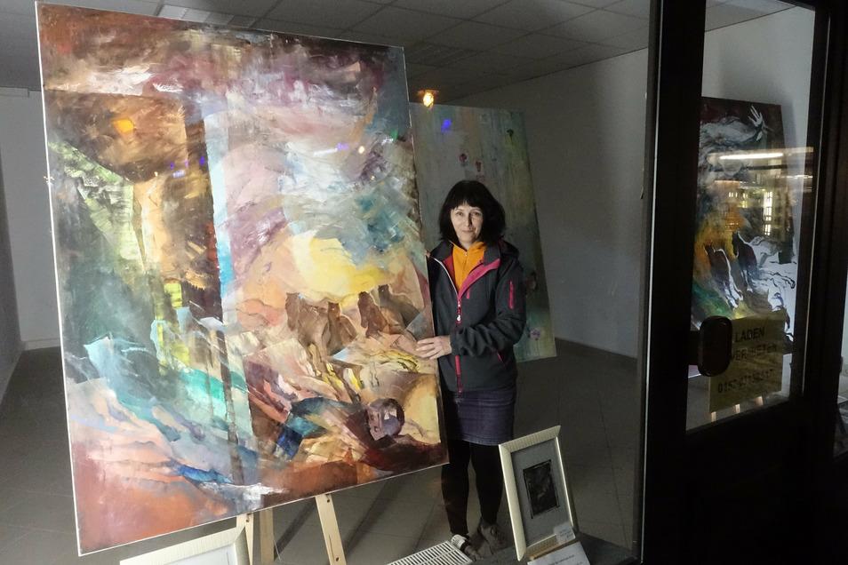 Olga Scheck stellt ihre großformatigen Bilder in einem Schaufenster an der Ritterstraße in Döbeln aus.