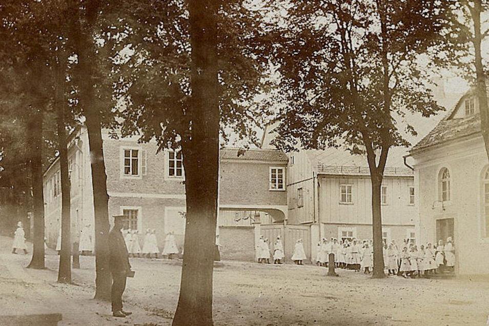 Das Foto vom Kirchgang der Schülerinnen der Mädchenanstalt entstand um 1920. Es zeigt auch das Schwesternhaus mit dem Holzfachwerk.