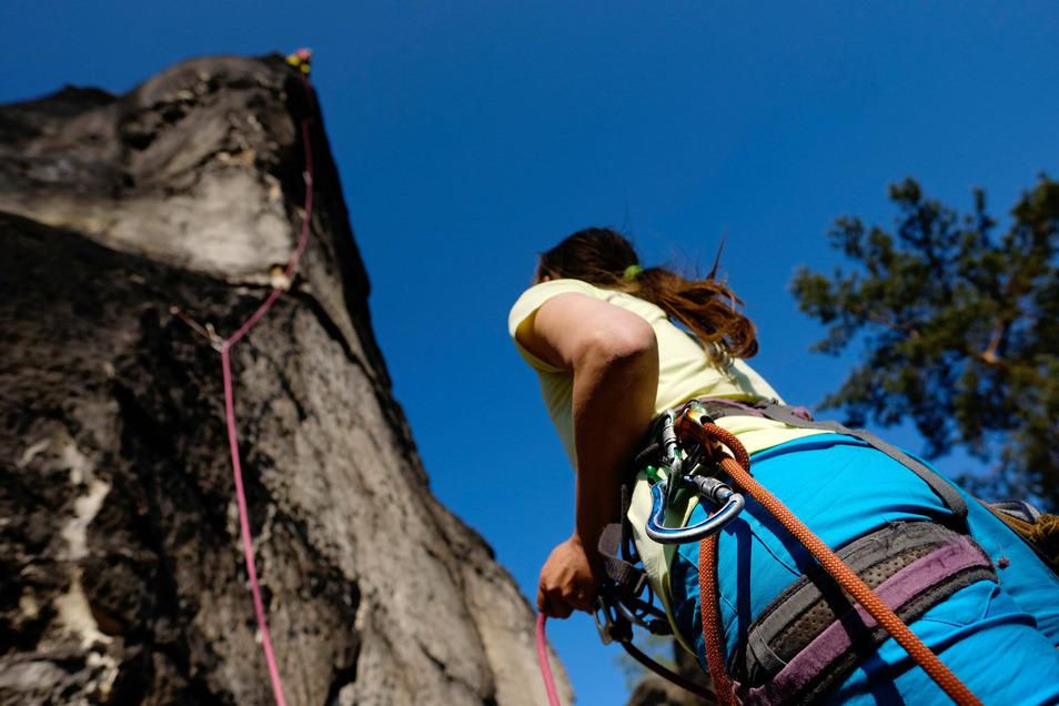 Viele wollen derzeit hoch hinaus: Eine Frau sichert einen Kletterer am Domwächter im Nationalpark Sächsische Schweiz.