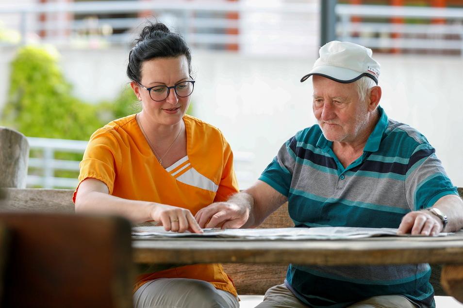 Doreen Pogarell und Tagespflege-Gast Rolf Sperling beim Lesen der Sächsischen Zeitung. In der Tagespflege der Herrnhuter Diakonie normalisiert sich das Leben langsam wieder.