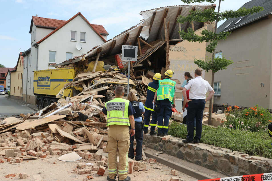 Einsatzkräfte stehen an der Unfallstelle in Altkirchen. Hier war gegen 06.15 Uhr am Freitagmorgen ein LKW in ein Haus gefahren.