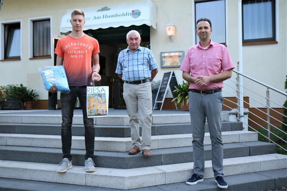 Mit kleinen Geschenken, unter anderem speziell gestalteten Badetüchern, beglückwünschten Riesas OB Marco Müller (r.) und SC-Trainer Horst Böhnisch (Mitte) den jetzt für den DSC startenden Riesaer Kevin Joite.