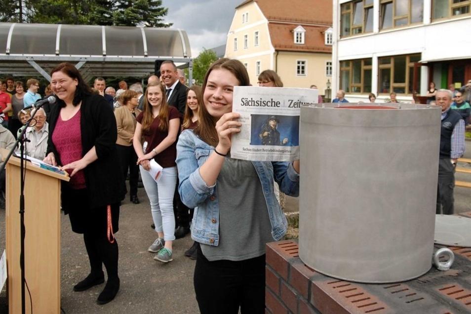 In den Grundstein ließen Schüler eine Zeitkapsel ein. Auch eine SZ ist darin, die Anika Hirschmann hineintut.