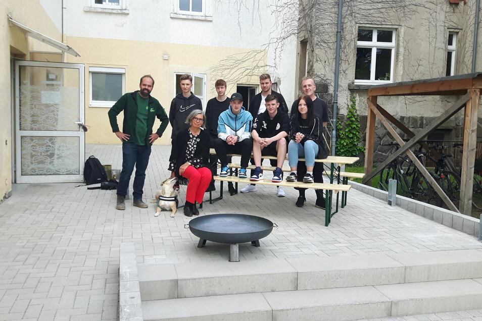 Zur Eröffnung des Jugendtreffs in Pulsnitz haben die Jugendlichen gleich die neuen Biertisch-Garnituren in Besitz genommen. Benjamin Richter von der Baufirma (l.), Bürgermeisterin Barbara Lüke (3.v.l.) und Betreuer Tom Schurig (r.) schauten auch vorbei