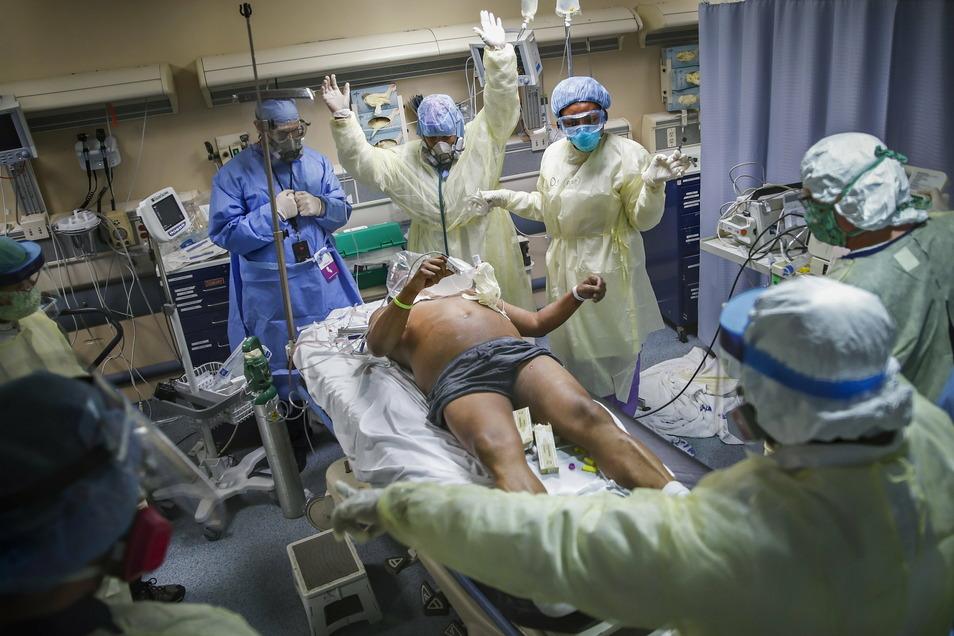 Krankenschwestern und Ärzte räumen den Bereich, bevor sie einen Covid19-Patienten defibrillieren, der im St. Joseph's Hospital in New York einen Herzstillstand erlitt.