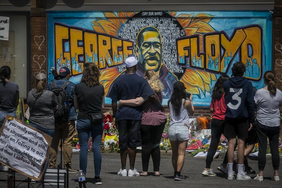Menschen stehen vor einem Wandgemälde, das in Gedenken an George Floyd gemalt wurde in der Nähe der Stelle, an der Floyd von der Polizei so brutal festgehalten wurde, dass er kurz darauf im Krankenhaus starb.