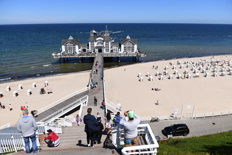 Touristen gehen im Ostseebad Sellin über die Seebrücke.