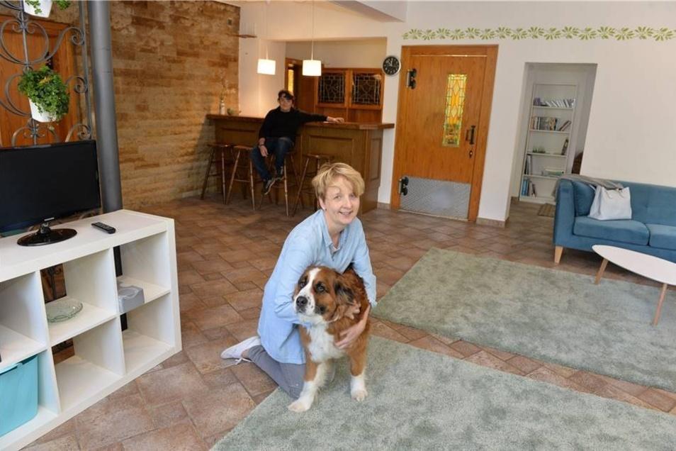 Maika Hochberger ist hier mit dem Hund Dala in der früheren Gaststube, jetzt das Gemeinschaftswohnzimmer.