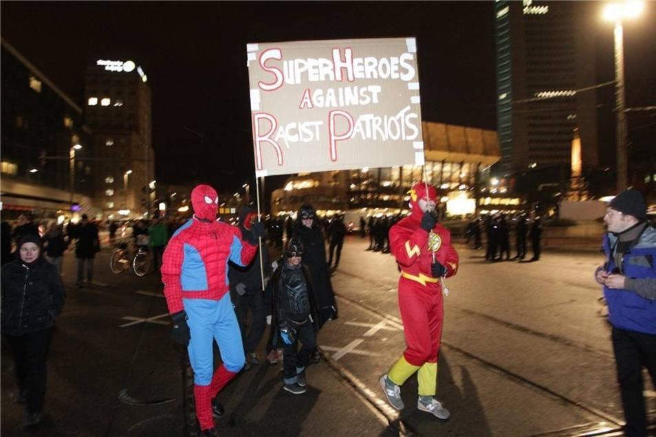 Zwei als die Superhelden Spiderman (l) und Flash Gordon verkleidete Gegendemonstranten.