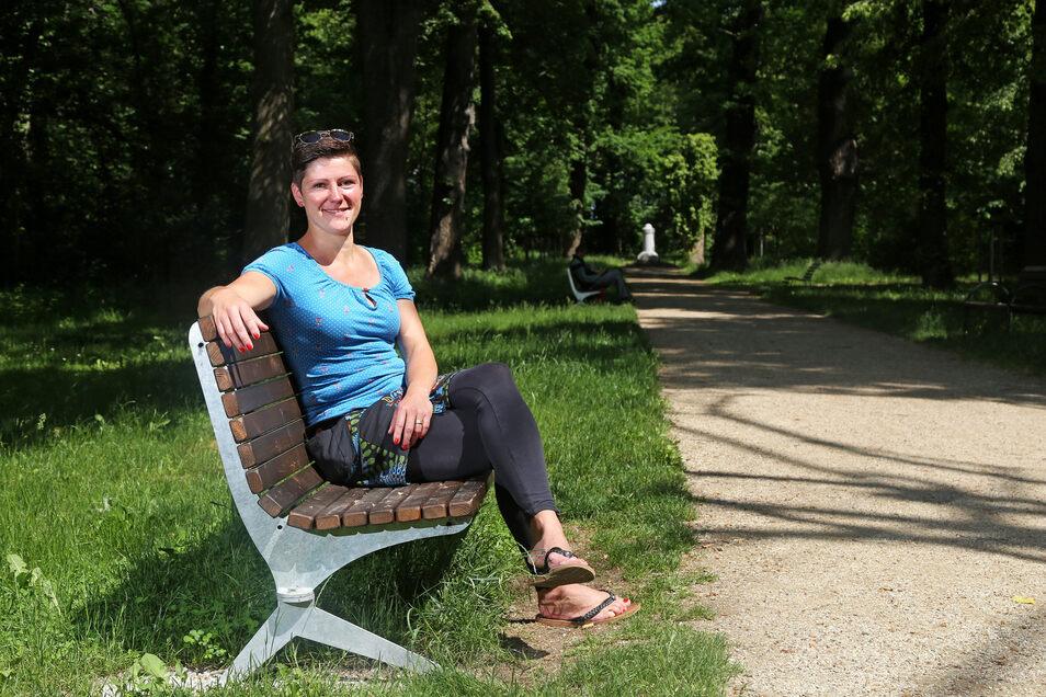 Susanne Braune auf einer der Bänke im Riesaer Stadtpark: Die 36-Jährige würde gern für weitere Sitzgelegenheiten im Park sorgen.