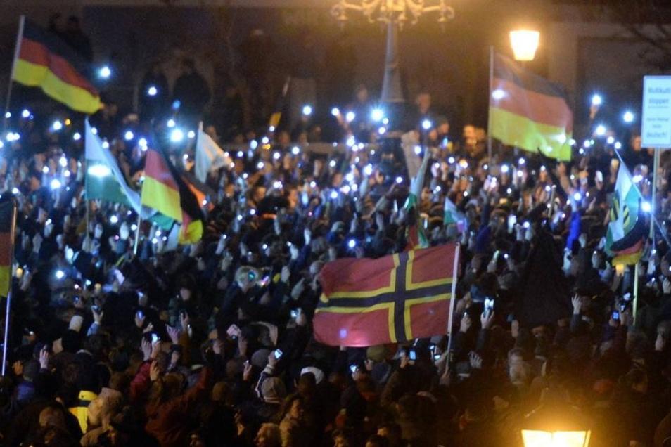 """Unter den Pegida-Anhängern hatten viele Deutschlandfahnen dabei. Doch auch eine deutlich zu erkennende Flagge der """"German Defence League"""" (GDL) war zu sehen. Die Fahne sieht auf den ersten Blick der Flagge Norwegens ähnlich, unterscheidet sich aber durch gelbe statt weißer Abgrenzungsstreifen. Die GDL ist eine rechtspopulistische Organisation, die unter Beobachtung des Verfassungsschutzes steht."""