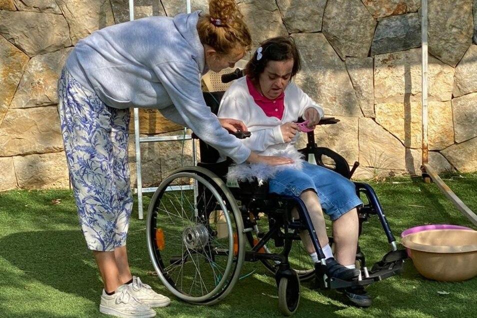 Eleni kümmert sich fürsorglich um eine Heimbewohnerin. Sie und ihre Kollegen nennen die behinderten Menschen lieber Gäste und behandeln sie entsprechend.