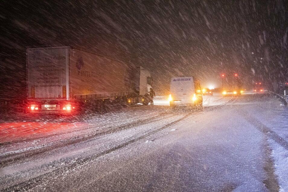 Lastwagen sind in der Nacht bei starkem Schneefall auf der A4 bei Siebenlehn unterwegs.
