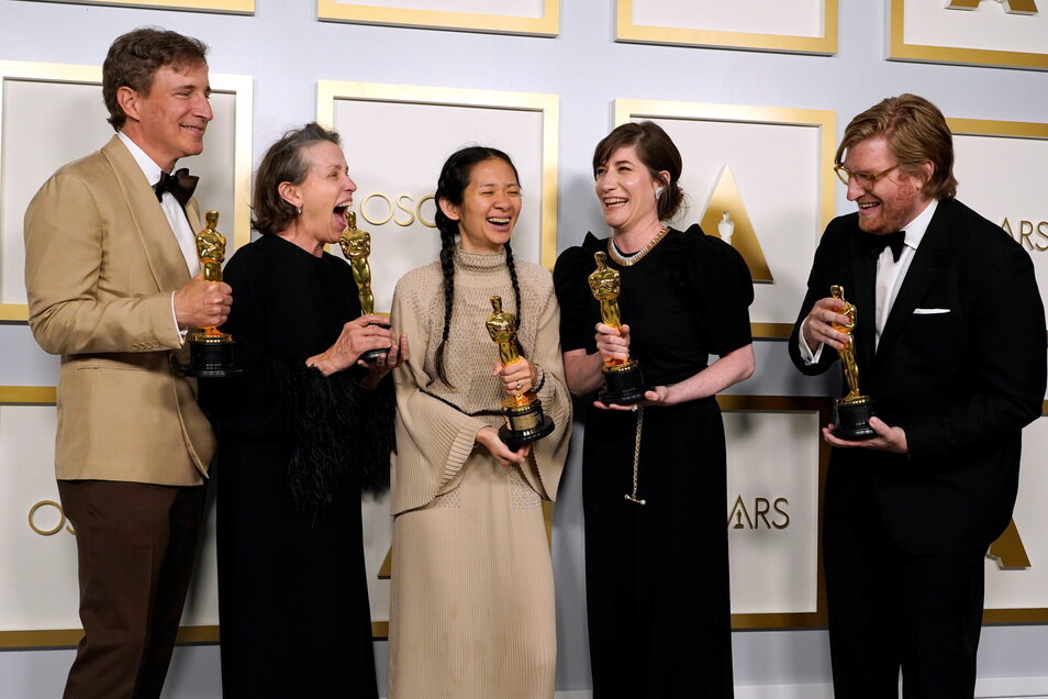 """Schauspieler und Filmproduzent Peter Spears (l-r), Schauspielerin Frances McDormand, Regisseurin Chloe Zhao, Filmproduzentin Mollye Asher und Produzent Dan Janvey mit dem Oscar für den besten Film für """"Nomadland""""."""