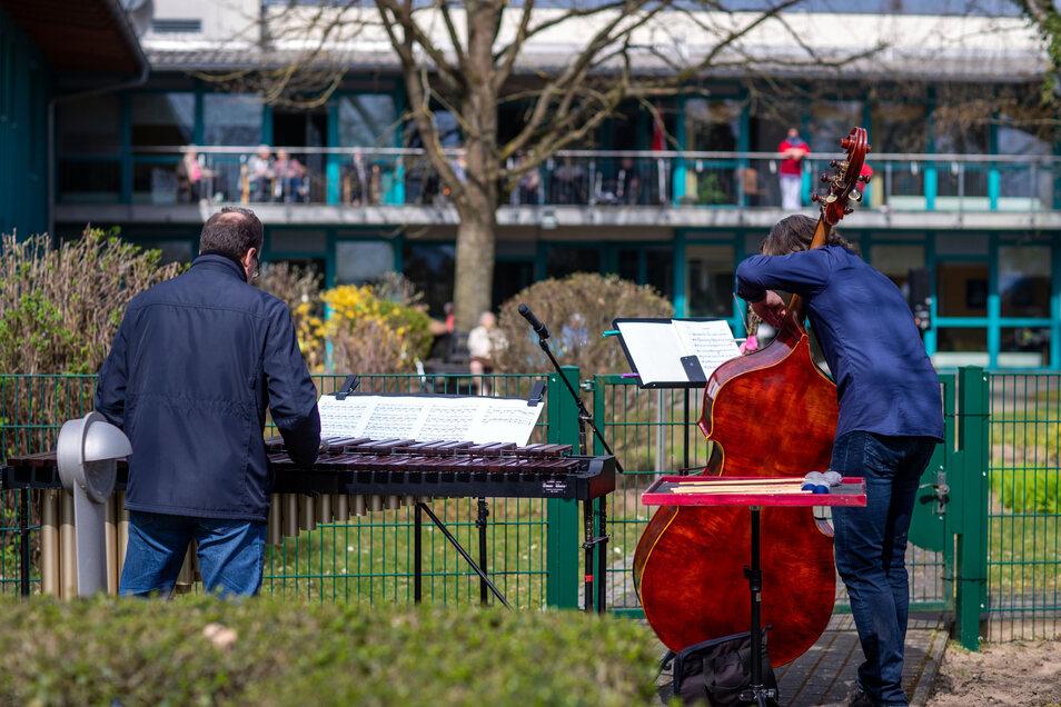 Musiker spielen ein kleines Konzert vor einem AWO Seniorenhaus.