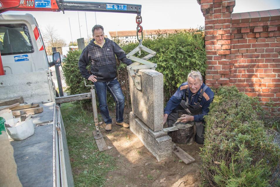Dietmar Natschke (rechts), Mitarbeiter im Steinmetzbetrieb Ertelt, befestigt auf dem Rothenburger Friedhof zusammen mit Hans-Jürgen Dittman den Gedenkstein zu Ehren des verdienstvollen Pfarrers Curt Zitzmann.