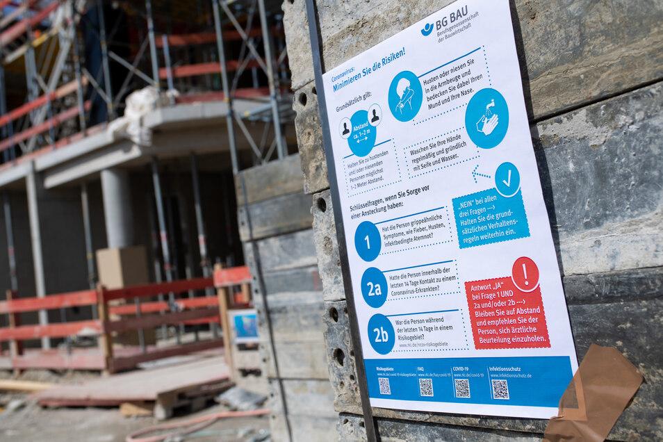 Schilder mit Corona-Informationen an einer Baustelle. Das Bauhandwerk scheint die Krise ganz gut zu überstehen. Anderen Handwerksbetrieben geht es auch im Landkreis Meißen schlechter.