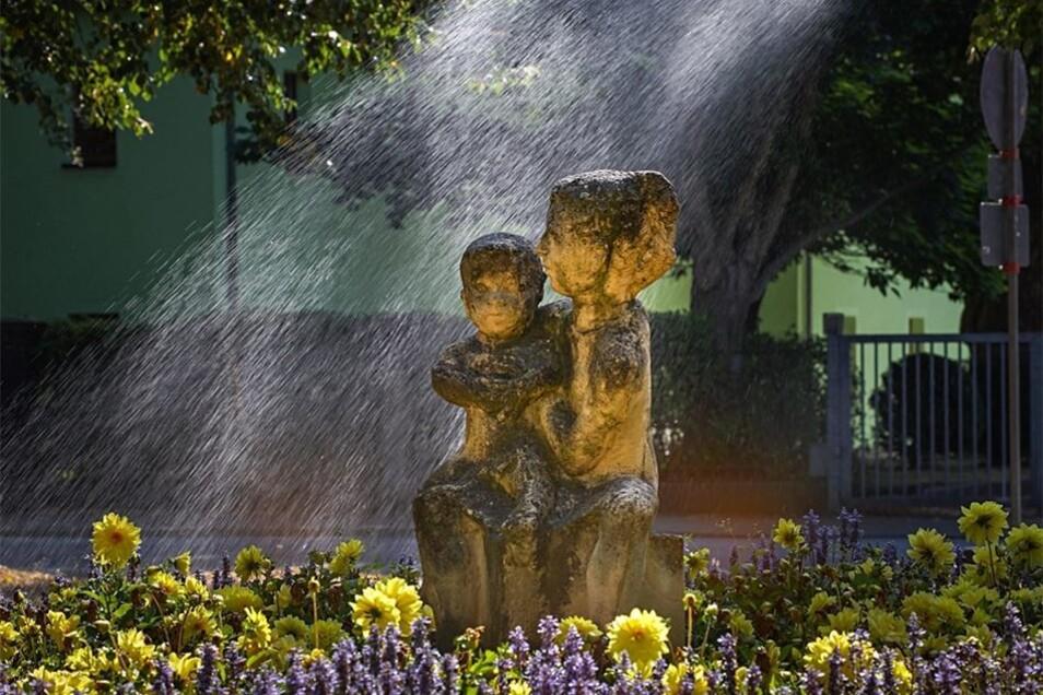 Unter der Dusche: Das Beet vor dem Kino in Bautzen wird samt Statue gegossen. Weil es so heiß und trocken ist, schauen die Mitarbeiter der BBB jetzt jeden Tag bei den Pflanzen vorbei.