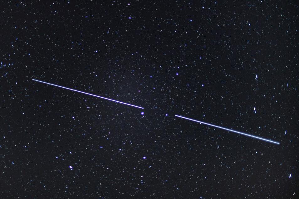 """Zwei """"Starlink""""-Satelliten sind als Lichtstreifen am Nachthimmel zu sehen (Aufnahme mit einer Belichtungszeit von 15 Sekunden)."""