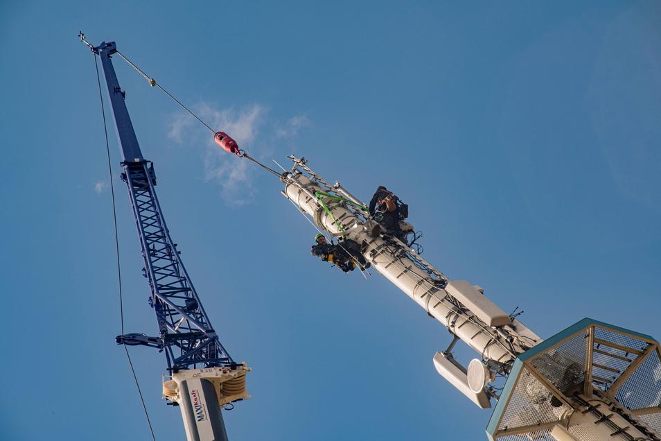 Am Telekom-Mast in der Berliner Straße in Großenhain steht derzeit ein Kran der Schwerlastlogistik Maxikraft. Was machen die Mitarbeiter am Mast?