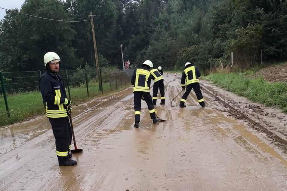 In Handarbeit begannen die Seifersdorfer Feuerwehrleute damit, den Schlamm von der Straße zu kehren.