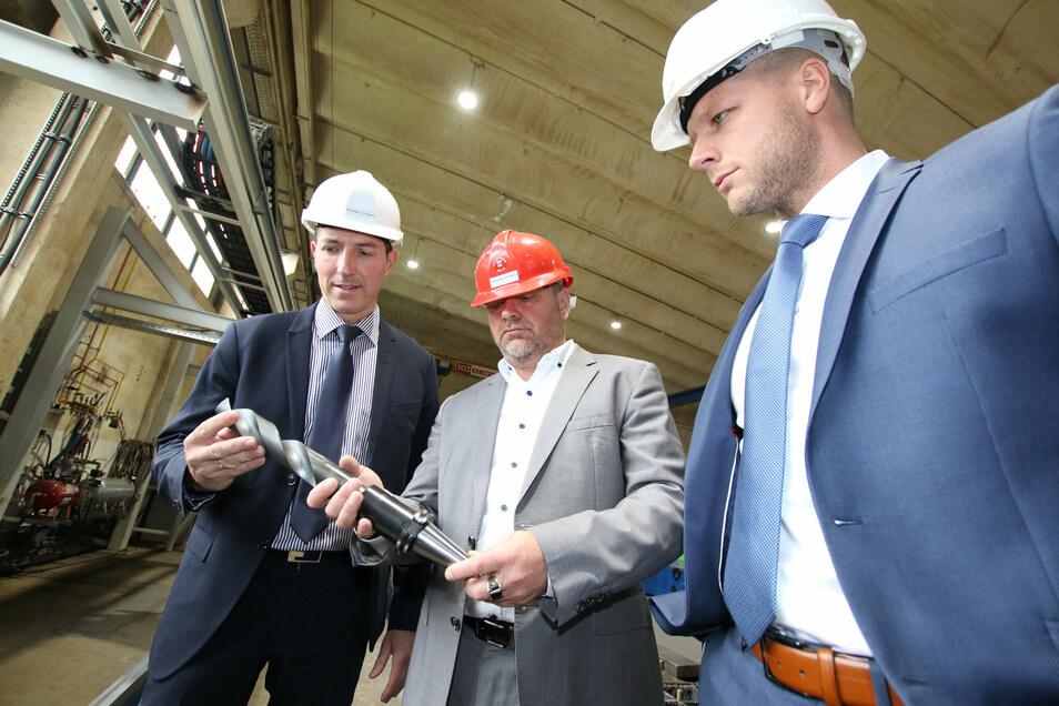 Stahlbau-Chef Andreas Gerth (Mitte) zeigt Sparkassen-Vorstand Thomas Gogolla (links) einen Bohrer, der zum neuen Blechbearbeitungszentrum gehört.