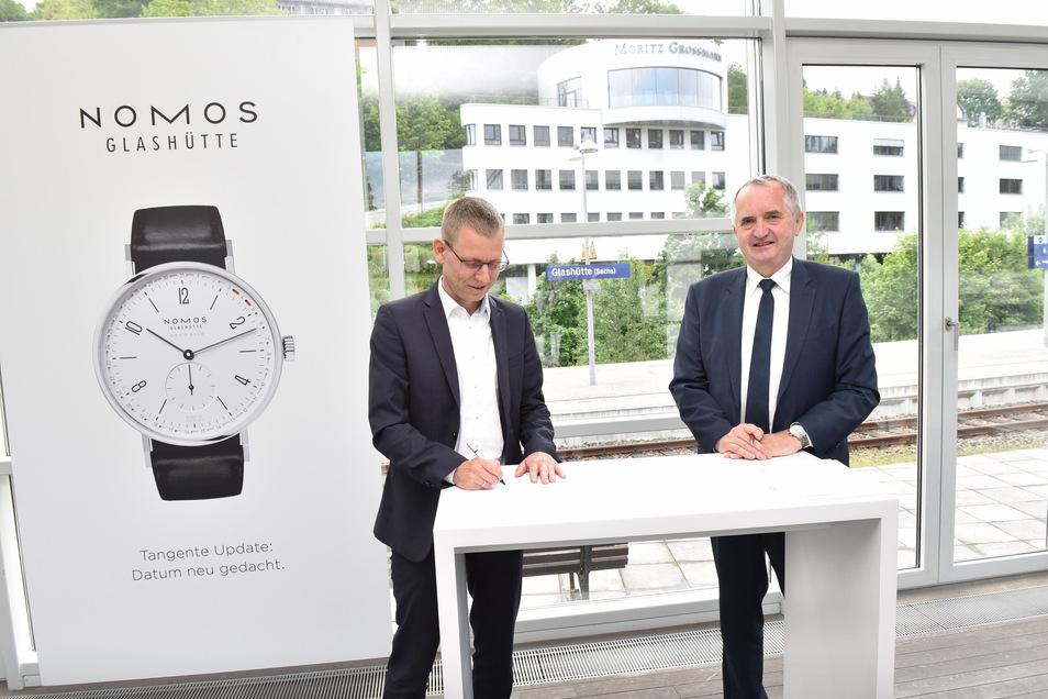 Glashüttes Bürgermeister Markus Deßler (li.) und Sachsens Minister für Regionalentwicklung Thomas Schmidt (beide CDU) unterzeichnen in der Uhrenmanufaktur Nomos den Vertrag, der Glashütte 150.000 Euro zusichert.
