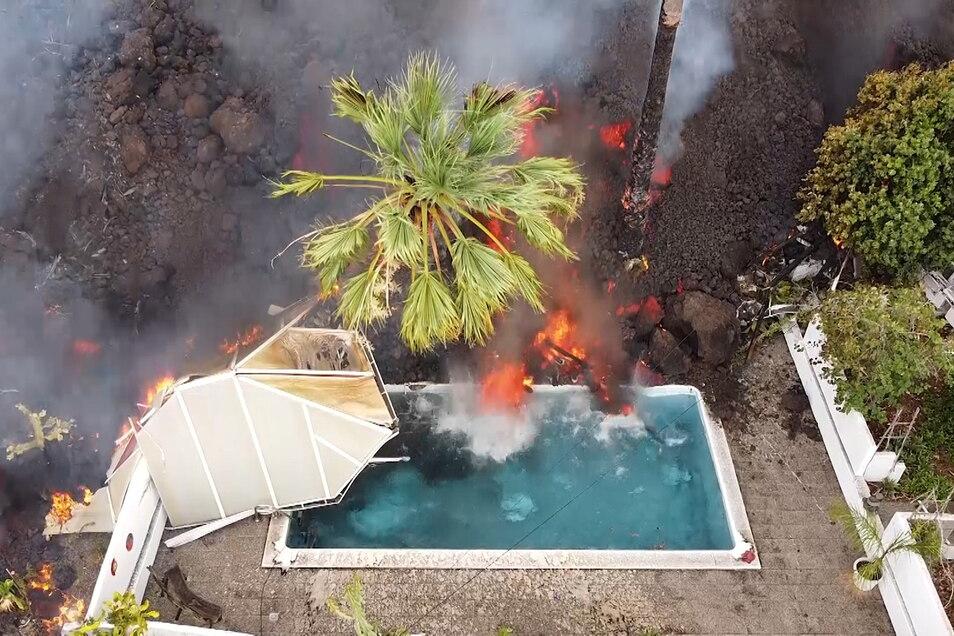 Ein Haus und ein Swimmingpool werden nach dem Vulkanausbruch von der Lava begraben.