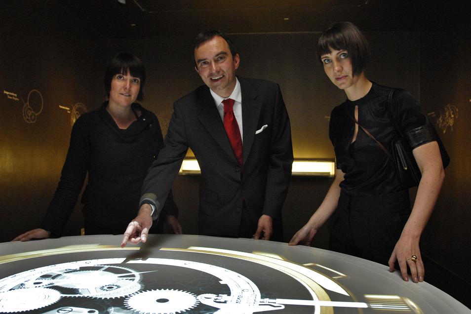 Geschäftsführer Dr. Frank Müller und die Architektinnen Britta Nagel (links) und Wenke Merkel aus Stuttgart schauen sich nach der Eröffnung ein Video vom Innenleben einer Glashütter Uhr an.