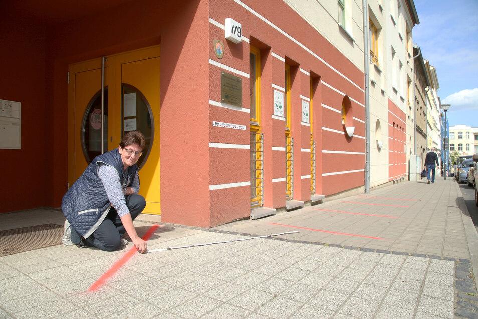 """Elvira Kühn markiert vor dem Eingang zur Kita """"Kinderinsel Kunterbunt"""" in der Görlitzer Mittelstraße die Abstände, die Eltern einhalten müssen."""