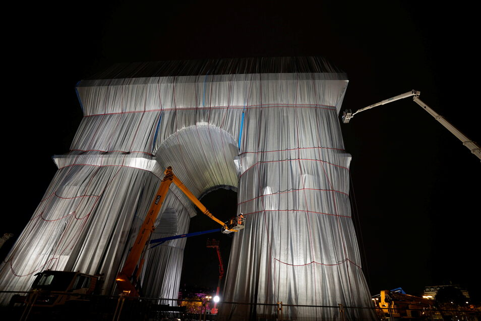 Arbeiter verhüllen den Triumphbogen in Paris.