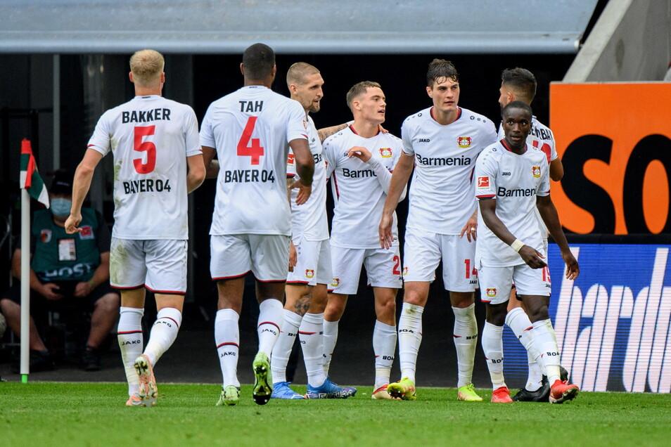 Die Spieler um Torschütze Florian Wirtz von Leverkusen (M) jubeln über den Treffer zum 1:4.