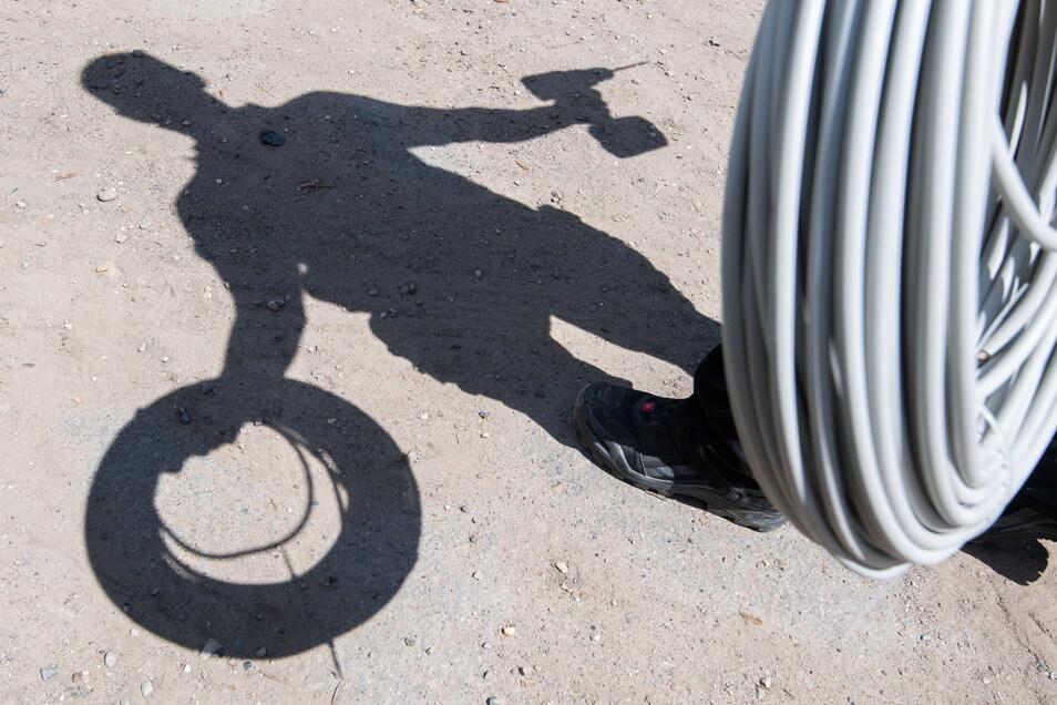 Ein Elektriker ist mit aufgerollten Kabeln und einem Akkuschrauber auf dem Weg zu einer Baustelle.