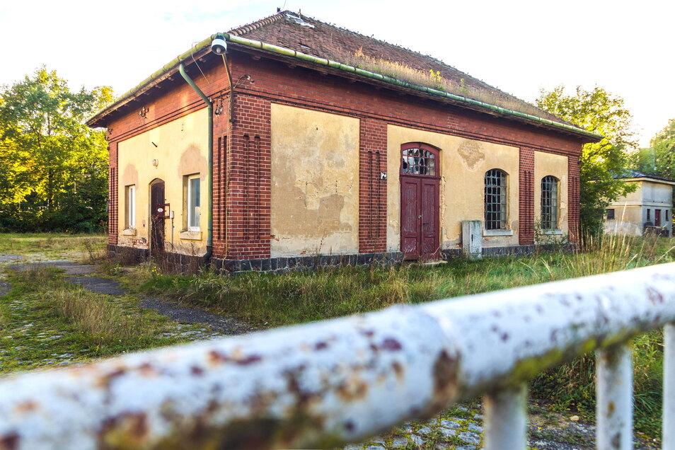 Das Brunnenhaus an der Merzdorfer Straße ist ein Denkmal. In Blickrichtung liegt hinter dem Gebäude die Feralpi-Arena, die Spielstätte von Stahl Riesa.