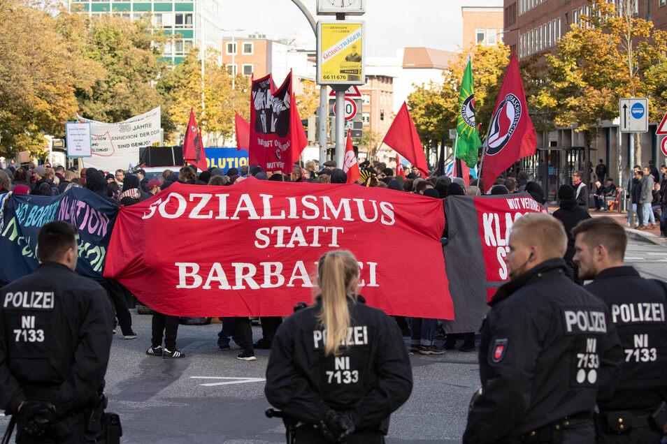 Polizisten begleiten zur gleichen Zeit eine Demonstration gegen die Einheitsfeier.