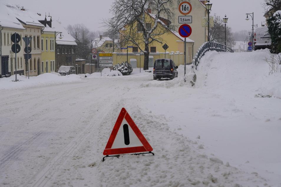 Ein Warnschild steht auf der Großenhainer Straße in Riesa. Ein Auto hat offenbar mitten auf der Straße ein Problem und kommt nicht weiter.