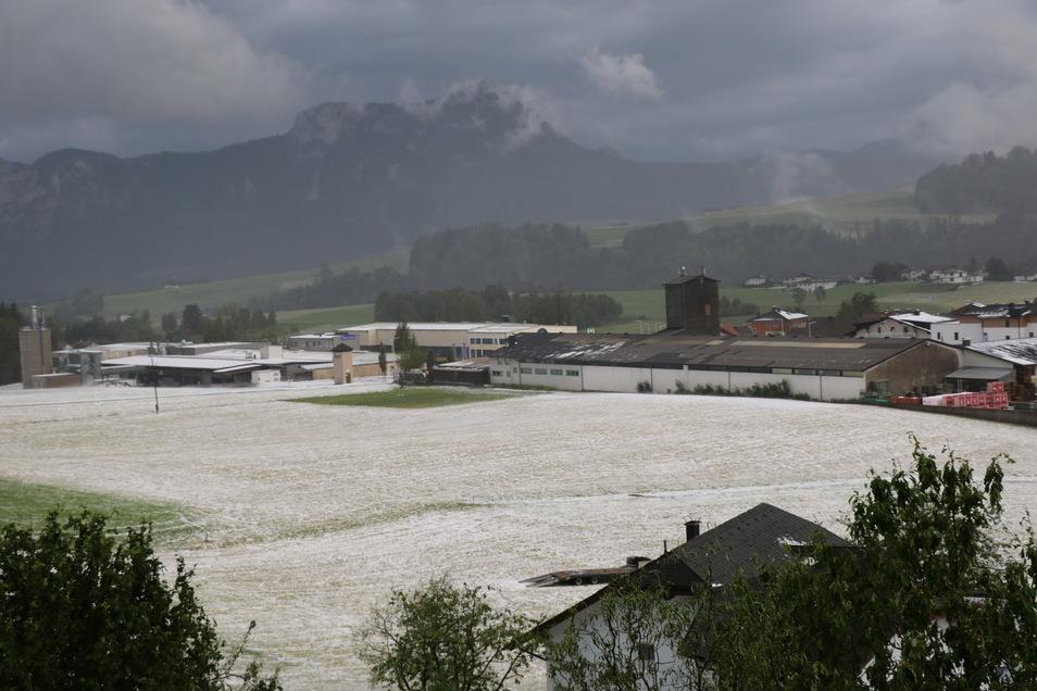 Österreich, Salzburg: Hagel liegt nach einem Unwetter auf einem Feld.